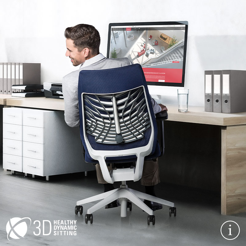 A young man sitting on a JOYCE chair in front of his desk in an office and looking to the side over his left shoulder, smiling. The JOYCE office chair is shown in rear view with blue mesh backrest, blue seat cover, black T-armrests and plastic parts (including base, column) as well as FlexGrid in white.  Further information is available via the information button at the bottom right | by Daniel Figueroa