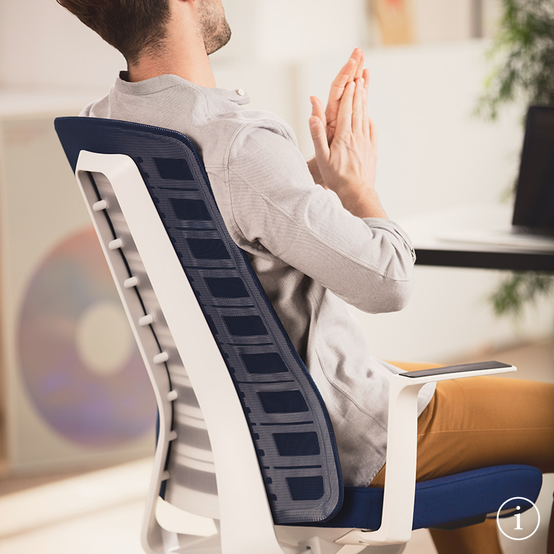 Young man, sitting on the PURE and using the unique opening in the upper backrest. The PURE ergonomic office chair is pictured from a side view with blue mesh backrest, blue seat cover, white arm pads, plastic parts and white column. Further information is available via the information button on the bottom right | by Andreas Krob & Joachim Brüske, b4k