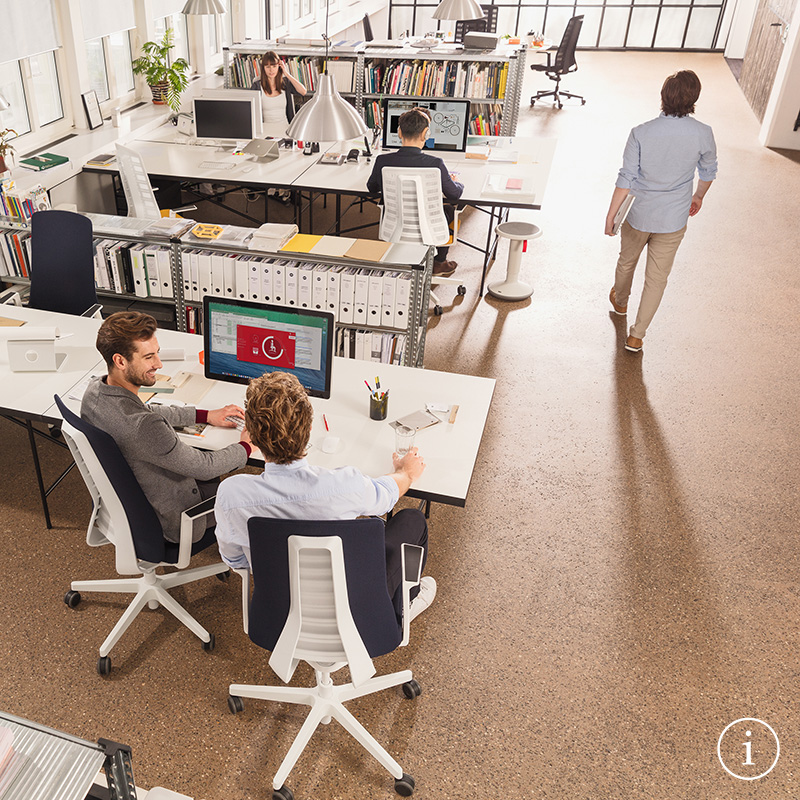Office space with PURE design office chairs at the desks. The PURE chairs are upholstered, mesh-covered and have blue, white and black backrest and seat covers. The S4.0 sensor technology is being used on a screen | by Andreas Krob & Joachim Brüske, b4k