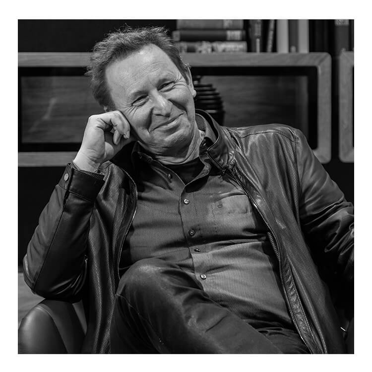 The designer of the SHUFFLEis1, Martin Ballendat, smiling and sitting on a chair, supporting his head with his hand. He is wearing jeans and a shirt with a leather jacket.